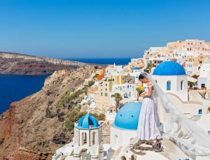 Bride with a bouquet of flowers, look at the sea, Santorini