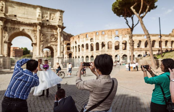 Rome, Italy - May 18, 2013: A group of Asiatic tourists take pictures to a marriage under the Coliseum, in Rome.